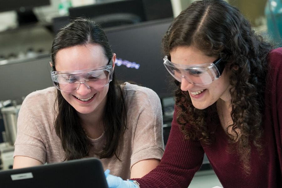 Two female students work in a lab at a computer.