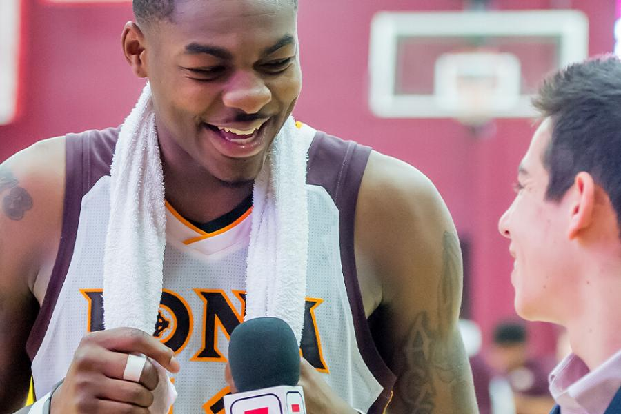 A male student interviews an Iona basketball player on the court after a game