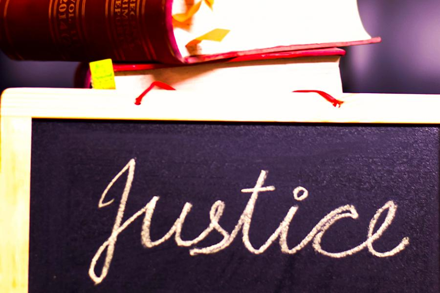 "A chalkboard with the word ""justice"" written on it and a book sitting on top of it."