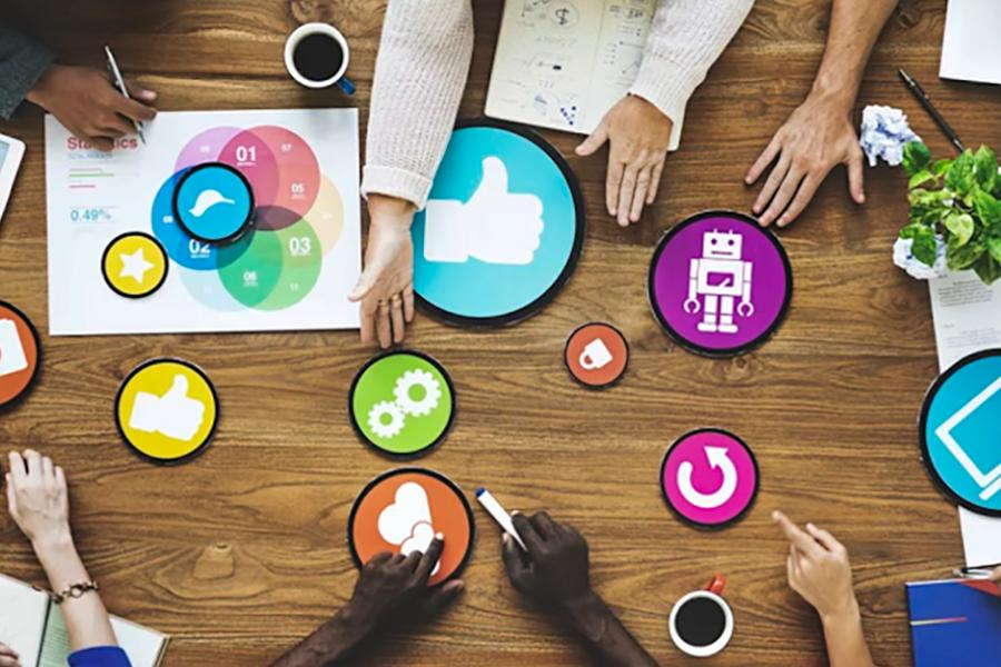 People collaborate on a table covered with circular marketing symbols.