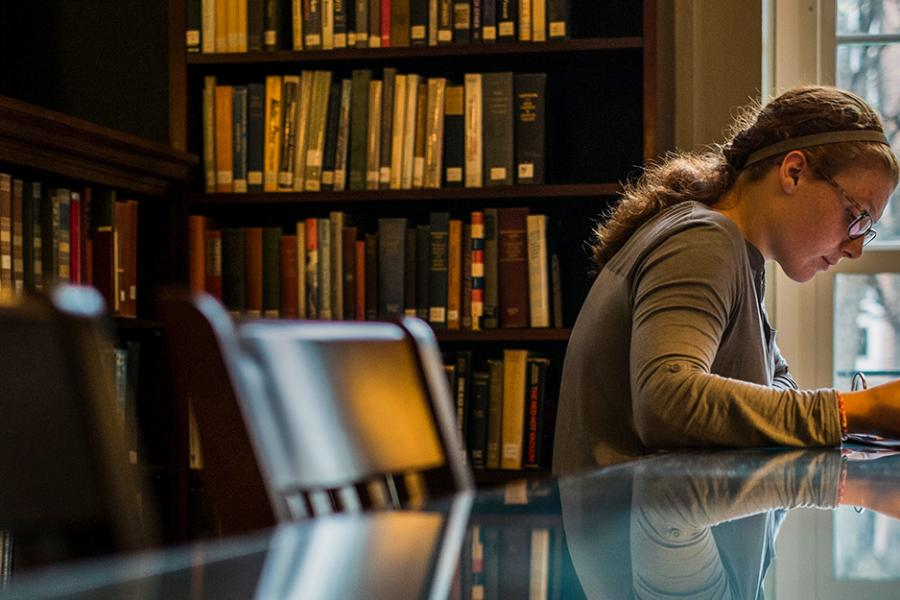 A female student studies by herself in the library.