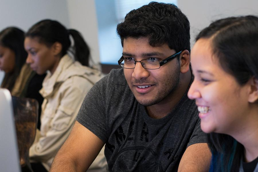 Two students work enthusiastically at an iMac in the computer lab.