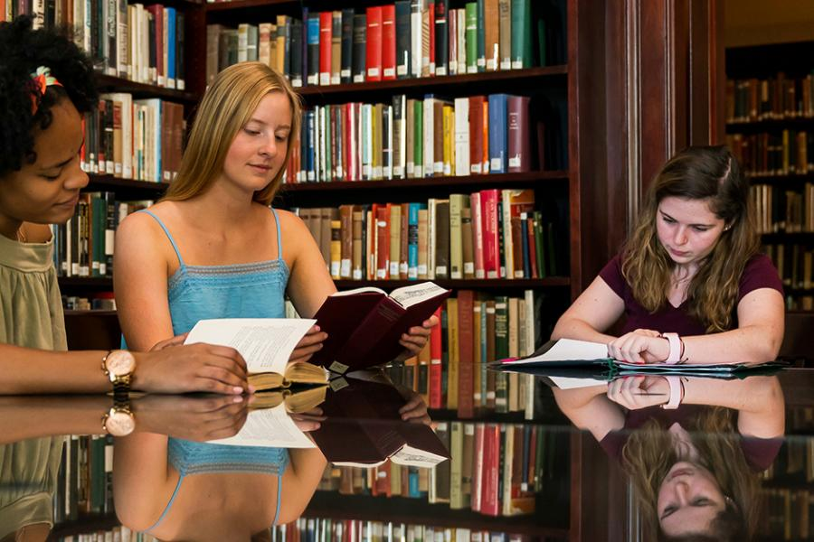 Three students sit at a table in the library reading books.