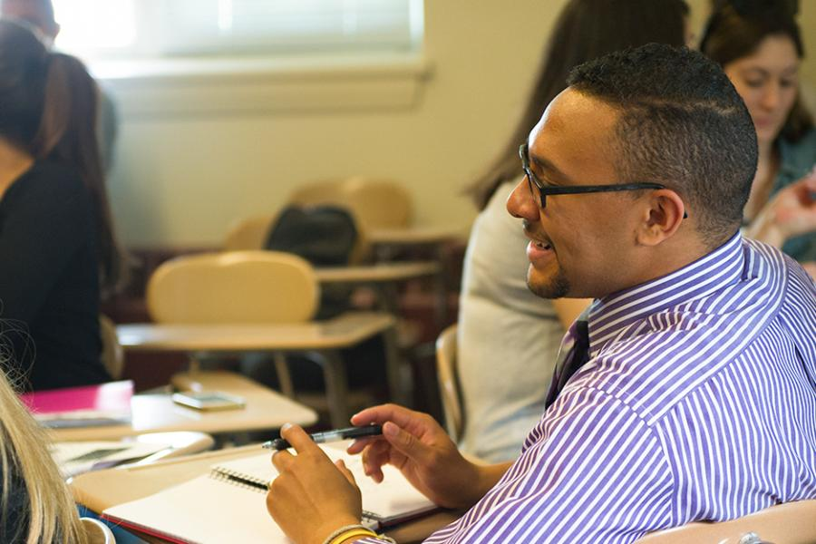 A student with glasses and a beard in a shirt and tie smiles in a psychology class.