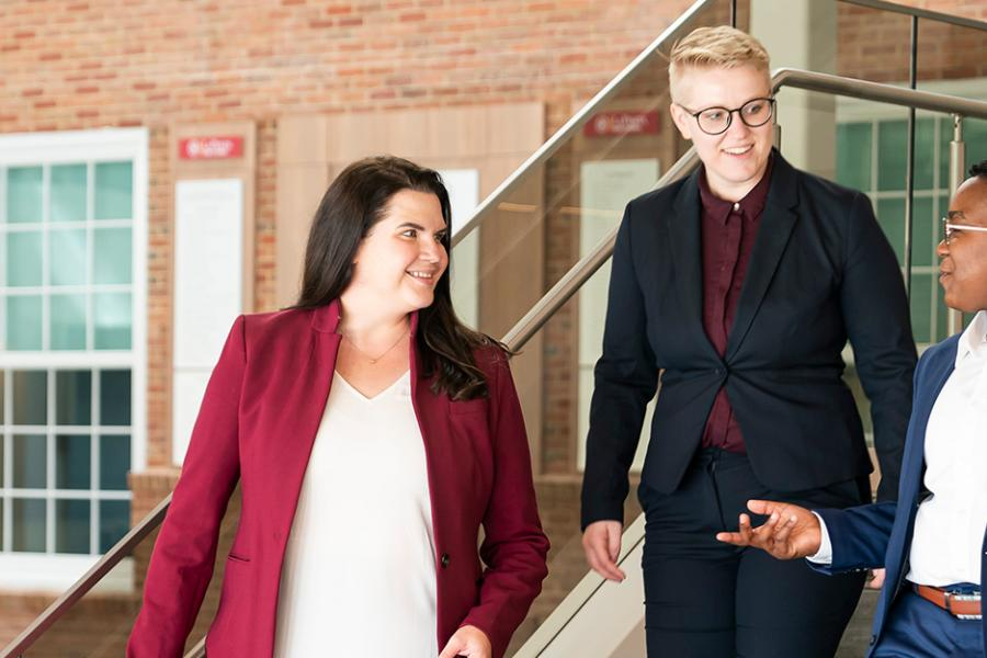 Three graduate students walk down the stairs in the LaPenta School of Business.