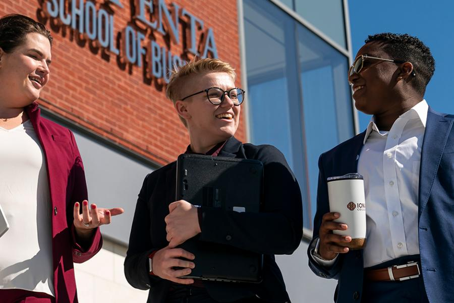 Three graduate business students walk in front of the LaPenta School of Business building on a sunny day.