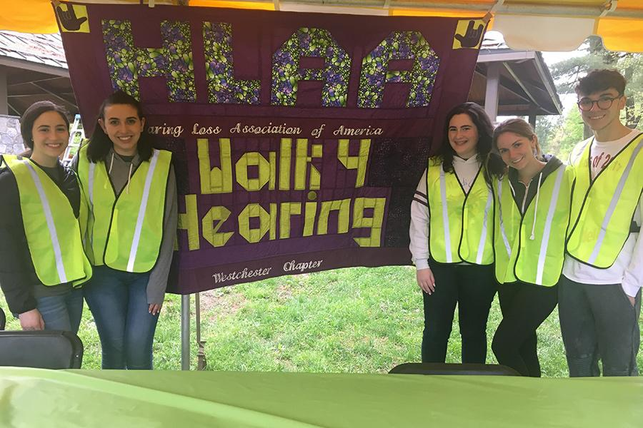 Iona College ASL club standing in front of the HLAA Walk for Hearing sign.