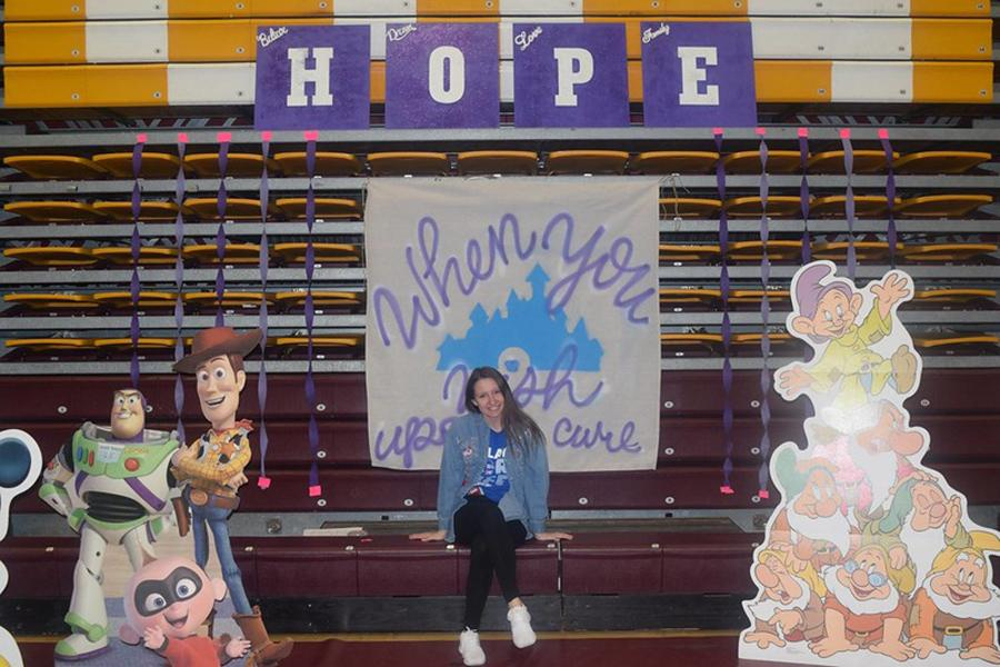 A member of Colleges Against Cancer sits under a sign that says hope and a banner that says when you wish upon a cure.