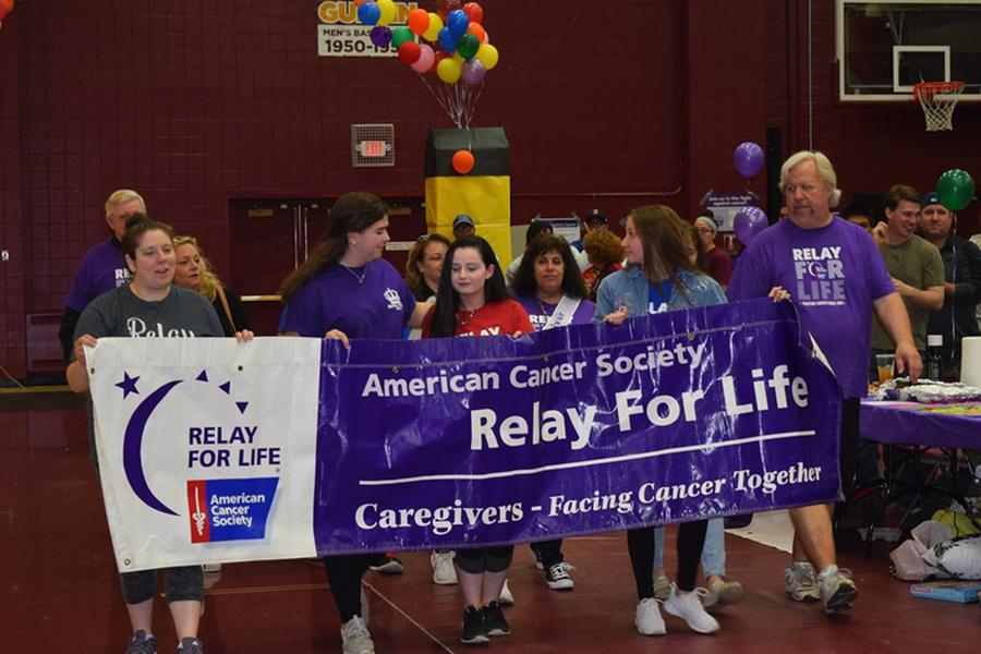 Members of Colleges Against Cancer hold a Relay for Life banner in the gym.