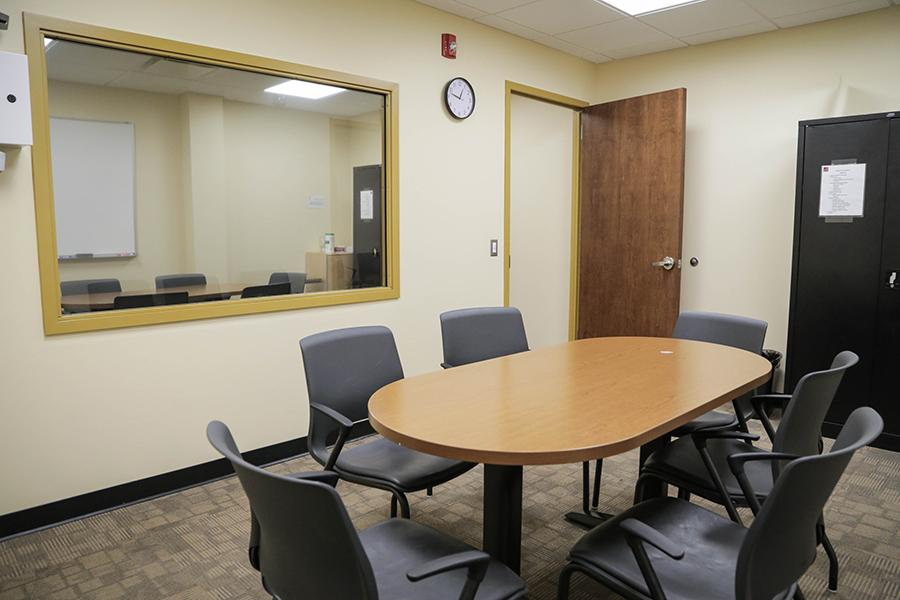 The group therapy room has an oval table in the middle and 6 chairs. There is a two way mirror so that family members can observe.