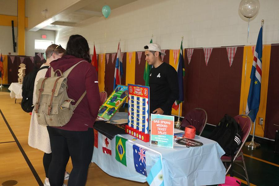 Two students talk with a member of the Iona International Club at the involvement fair.