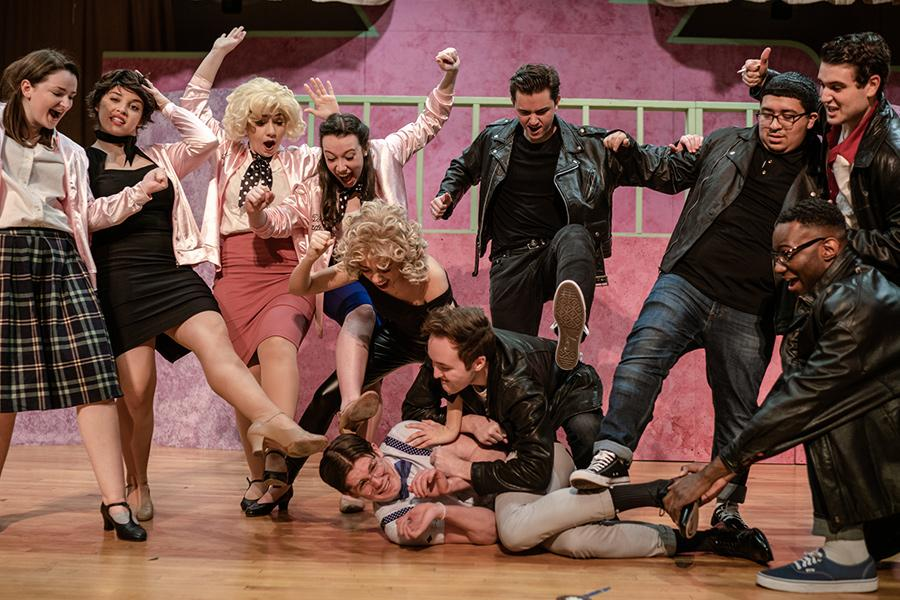 Members of a gang in the musical Grease pick on someone in a dance number.