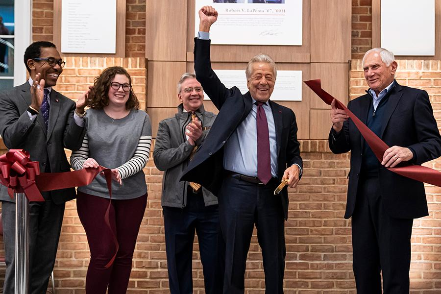 Robert LaPenta raises his fist in victory at the LaPenta School of Business ribbon cutting.