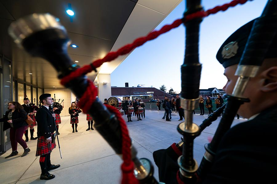 Pipers play outside of the LaPenta School of Business during the ribbon cutting.