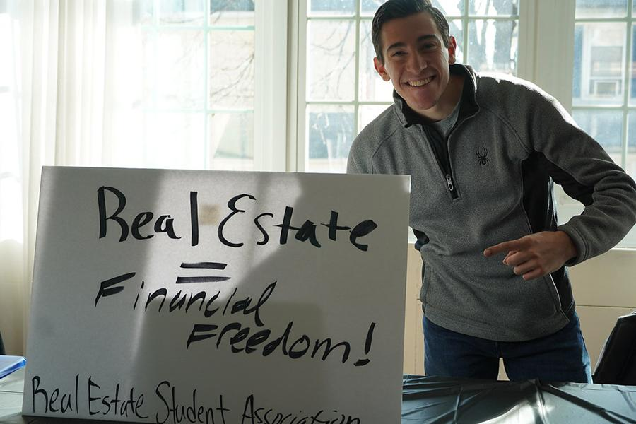 The president of the Real Estate Association posing with his sign for the club.