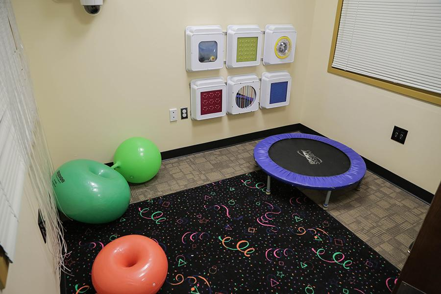 The sensory room has a small trampoline as well as large inflatable balls for children to interact with.