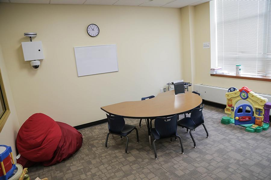 The treatment space for children has a small table with four small chairs, some red bean bags, and a variety of toys.