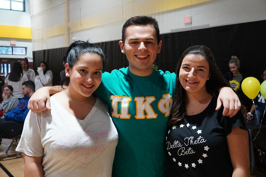 Two sorority members and a fraternity member smile at the involvement fair.