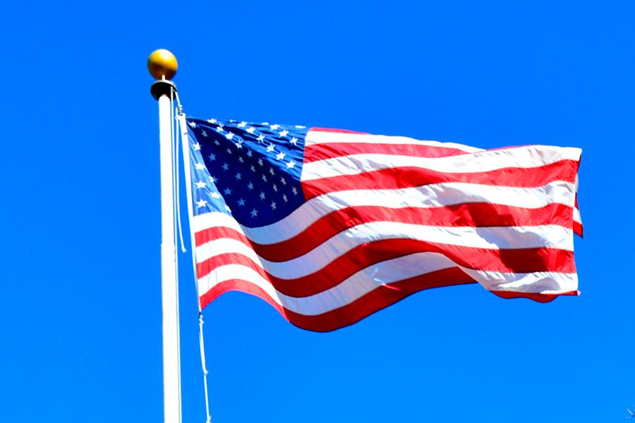 The American flag blows on the quad blows in the breeze in front of a blue sky.