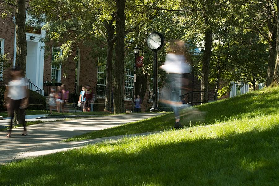 The exposure on the camera makes students walking by appear blurry and in a rush but the clock on campus is clear.