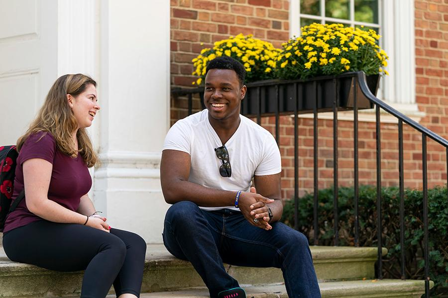 Two Iona students sit on the steps of the advising center and talk.