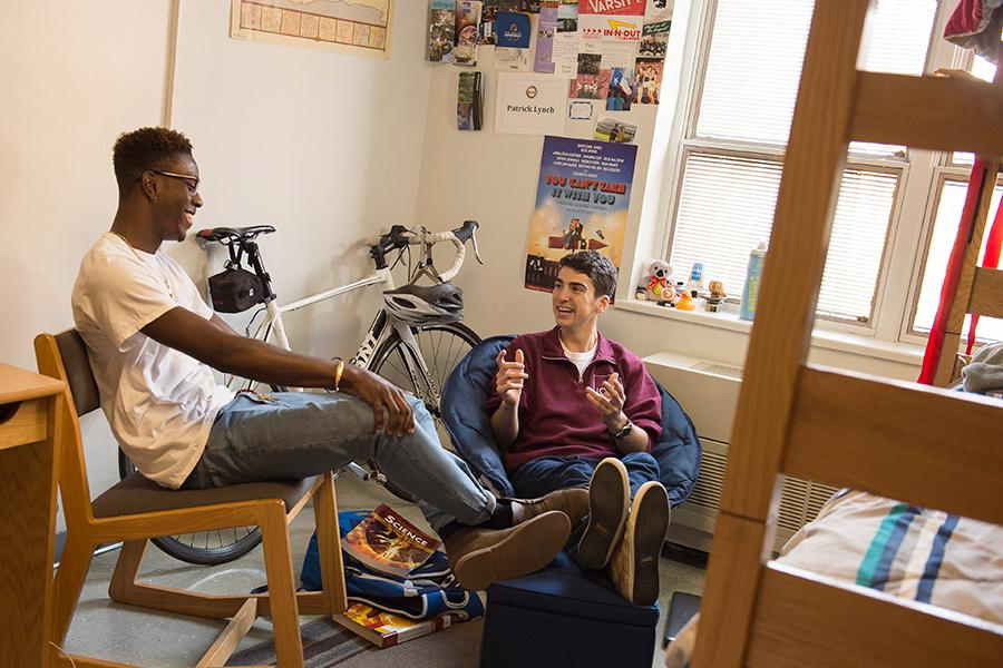 Two students smile and have a conversation in a Living Learning Community dorm room.
