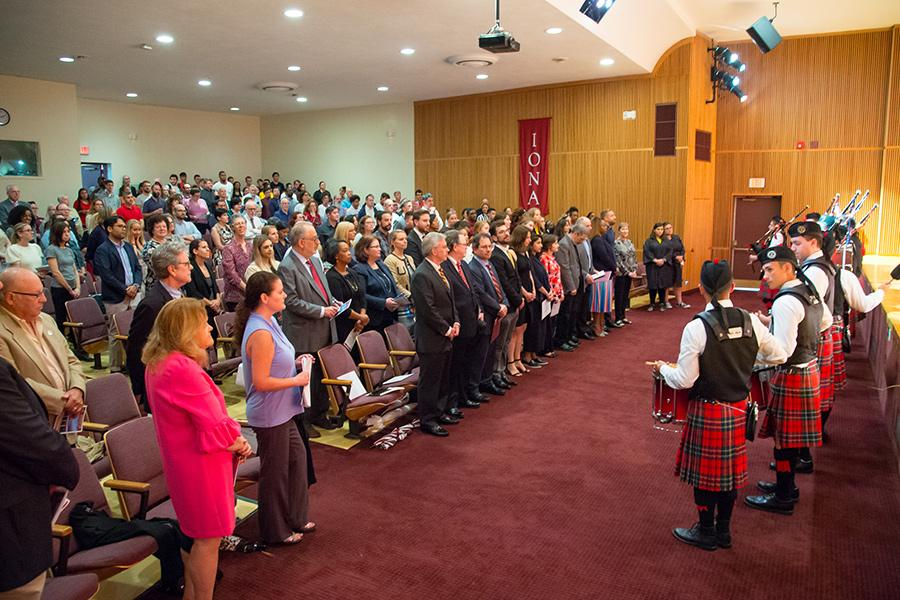 Faculty, staff and students gather at an event in the auditorium while the pipers play.