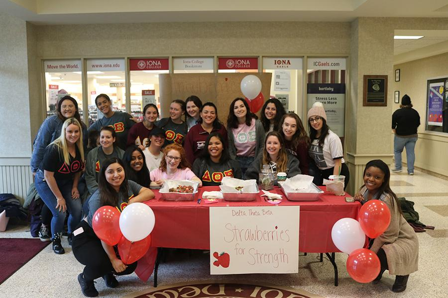 Several members of the Delta Theta Beta sorority sell chocolate covered strawberries to raise money for charity.