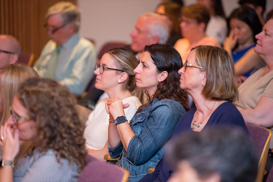 Members of the faculty listen intently at a college meeting.