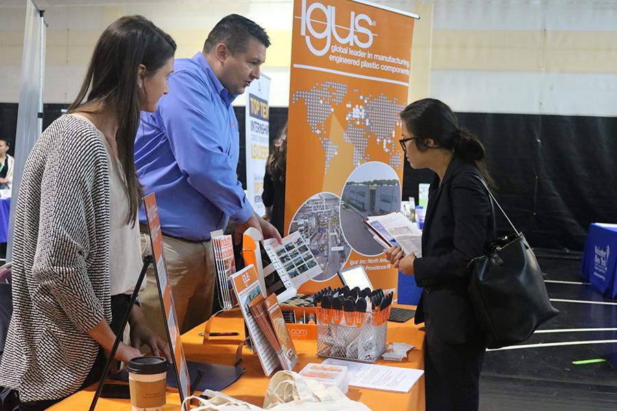 A student chats with 2 representatives from Igus at the career fair.