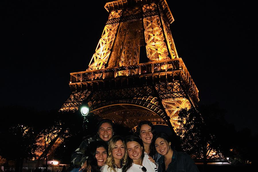 A group of Iona students in front of the Eiffel Tower at night in Paris, France.