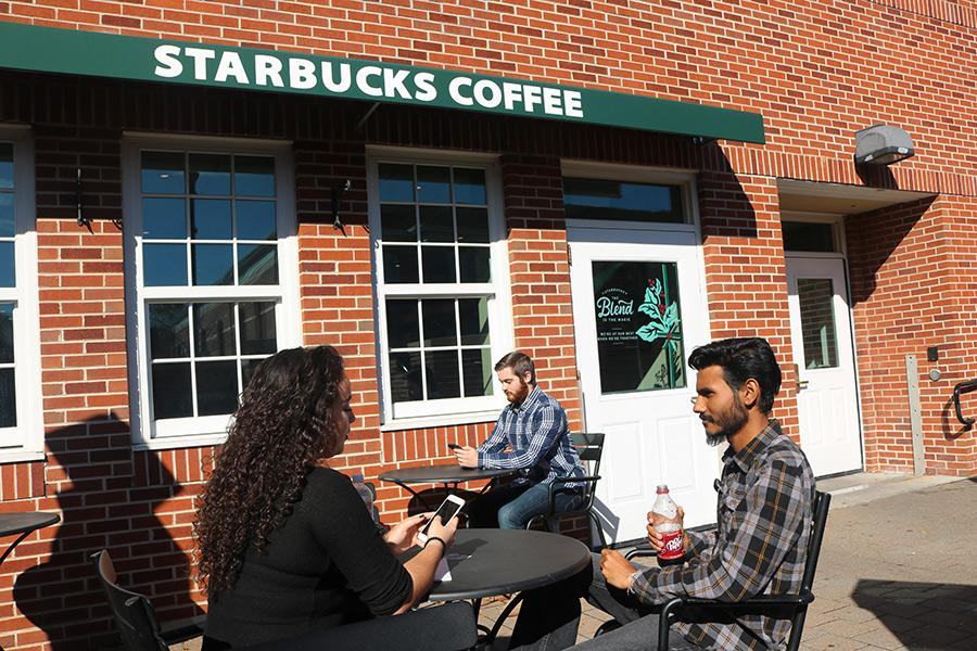 Students chatting outside of Starbucks are enjoying the sunny weather.
