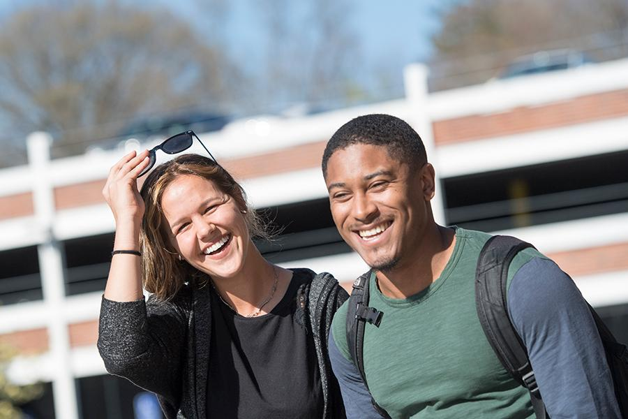 Two graduate students smile and laugh near the parking garage on campus.