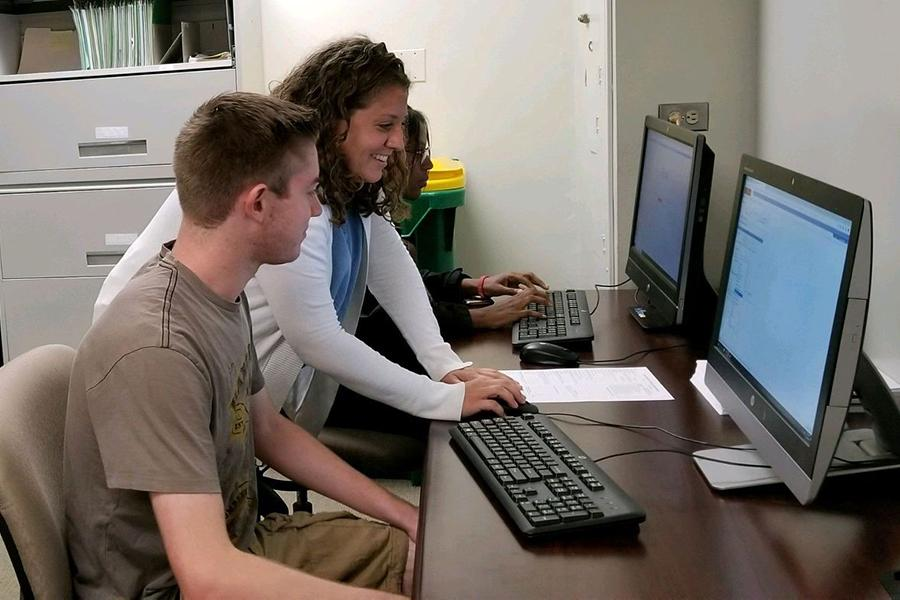 Nicole from the advising center helps a student create his schedule at one of their computer work stations.