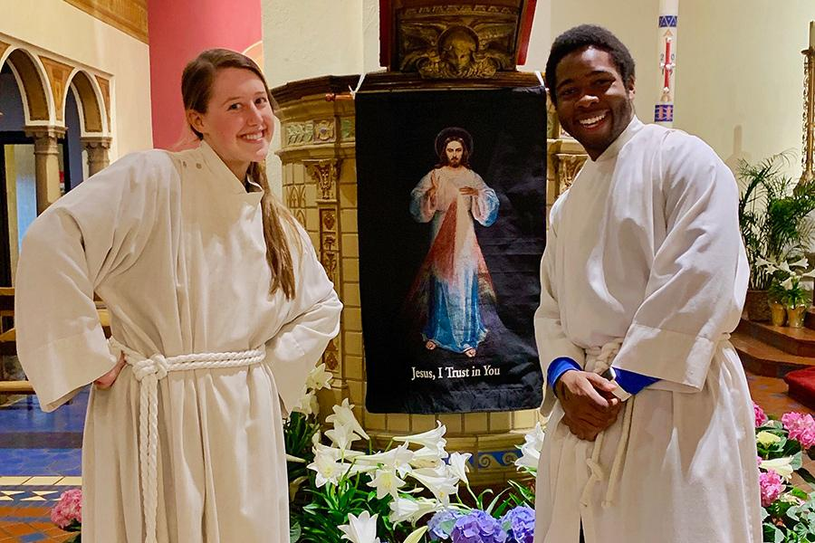 Two students where white robes to assist with Catholic mass with a painting of Jesus in between them.