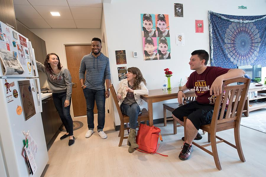 Four Iona students hang out in the kitchen area of their living learning community.