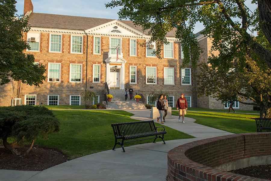 A student in an Iona hoodie leads two individuals on a campus tour and walk past Doorley hall.