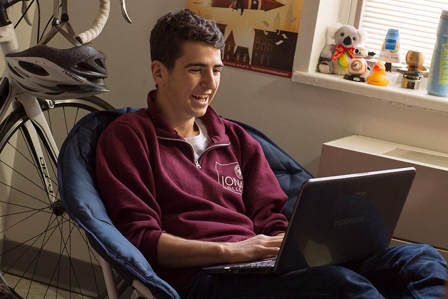 A student in an Iona shirt does a virtual information session on his laptop.