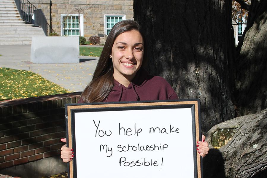A student smiles and holds a sign that says You help make my scholarship possible.