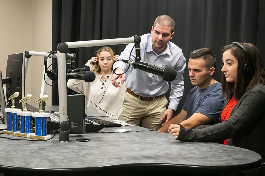 Three students sit around the podcast station, complete with soundboard and microphones, as their professor explains how to use the equipment.