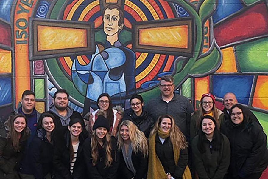 Iona students stand in front of a mural of Blessed Edmund Rice on the Ireland mission trip.