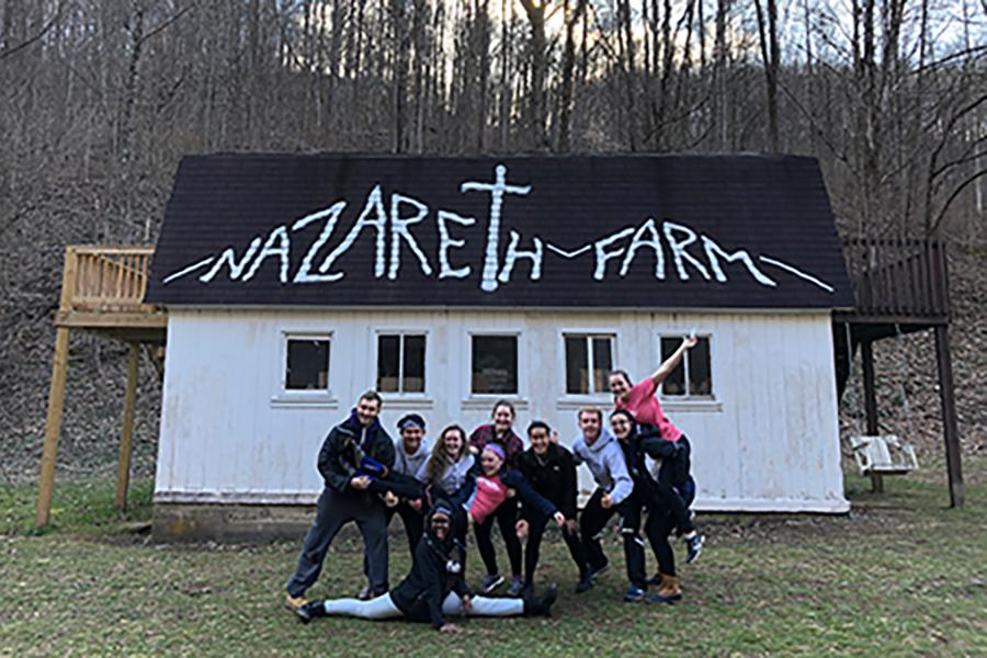 A group of students stand together in front of a building at Nazareth Farm in West Virginia.
