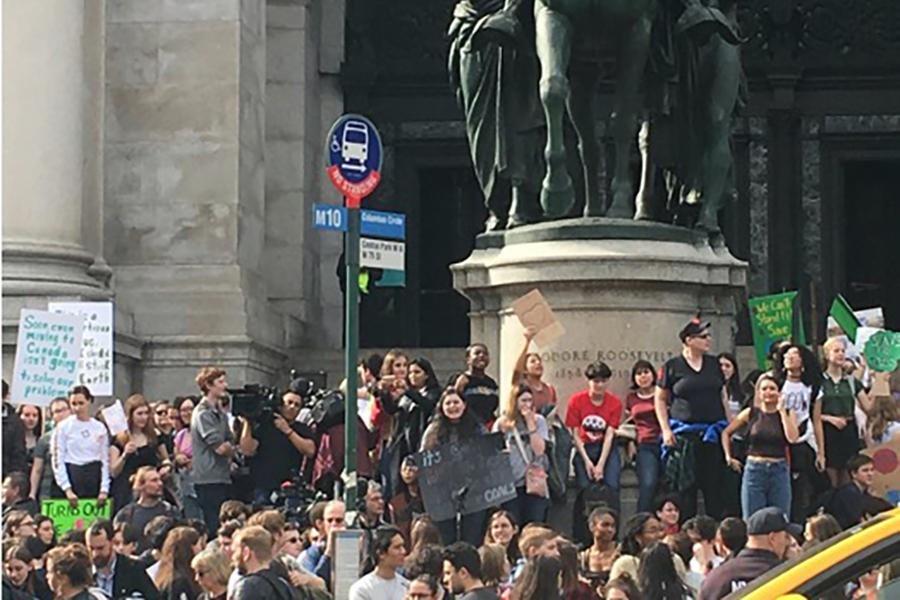 Demonstrators gather in a crowd in front of a statue to raise awareness for climate change.
