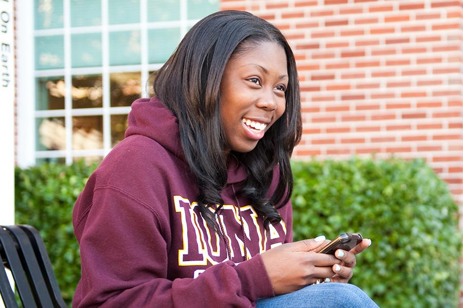 A student sits on a bench and smiles and scrolls through her phone.