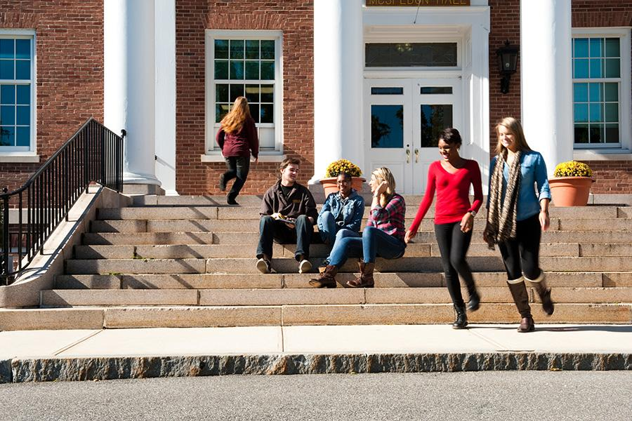 Three students sit on the steps while two students walk by and one student walks into the building.