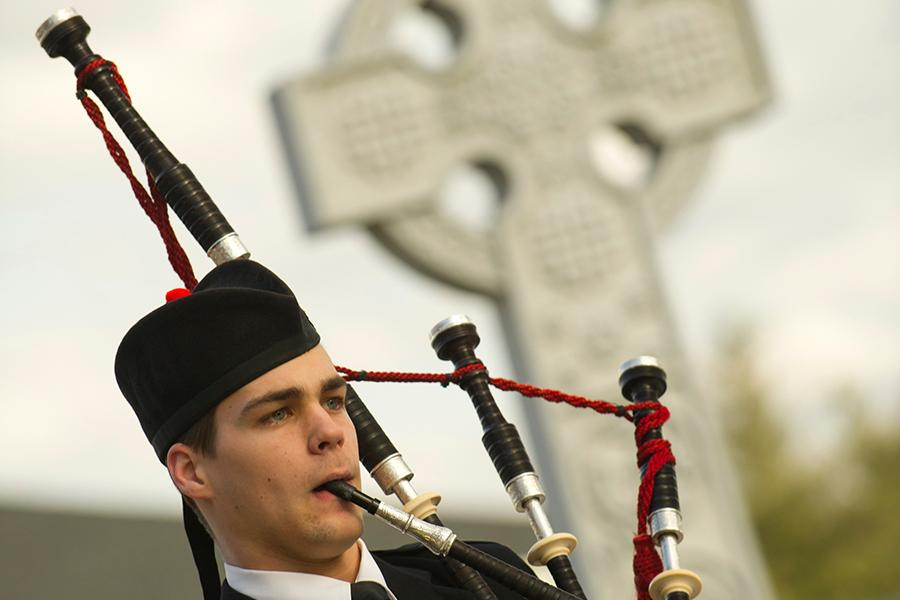 A piper plays bagpipes with the Celtic cross in the background.