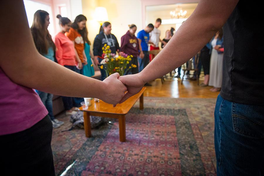 Members of the Iona Community hold hands in a circle and pray at the chapel