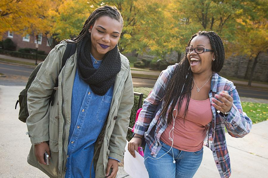 Two students smile, talk and laugh on their way to a class for health care management.