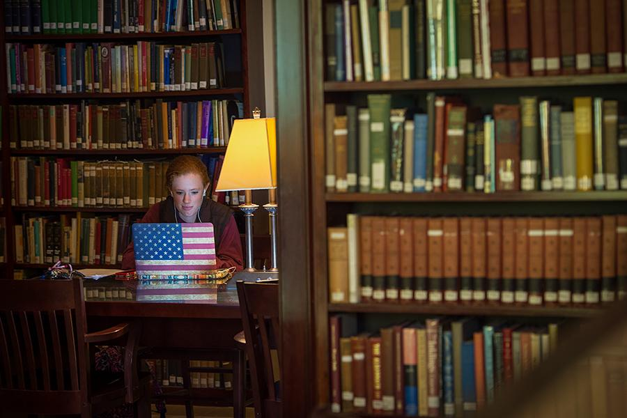 A student works alone in the library. Her laptop has an American flag overlay.