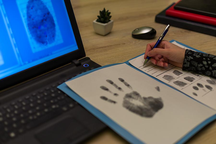A person writes on a piece of paper in a folder with fingerprints and a hand print.